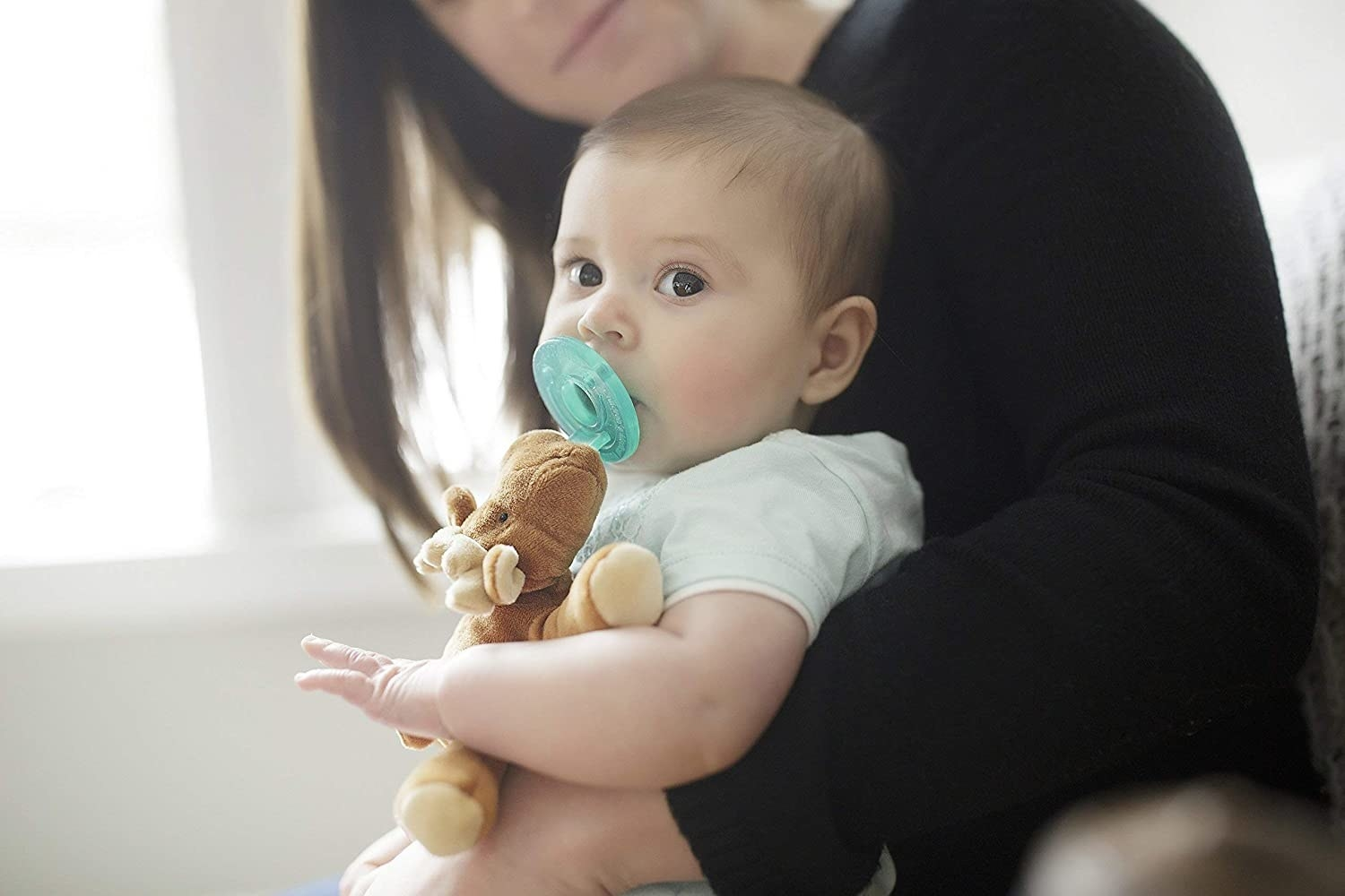 a baby with a moose plush attached to a pacifier