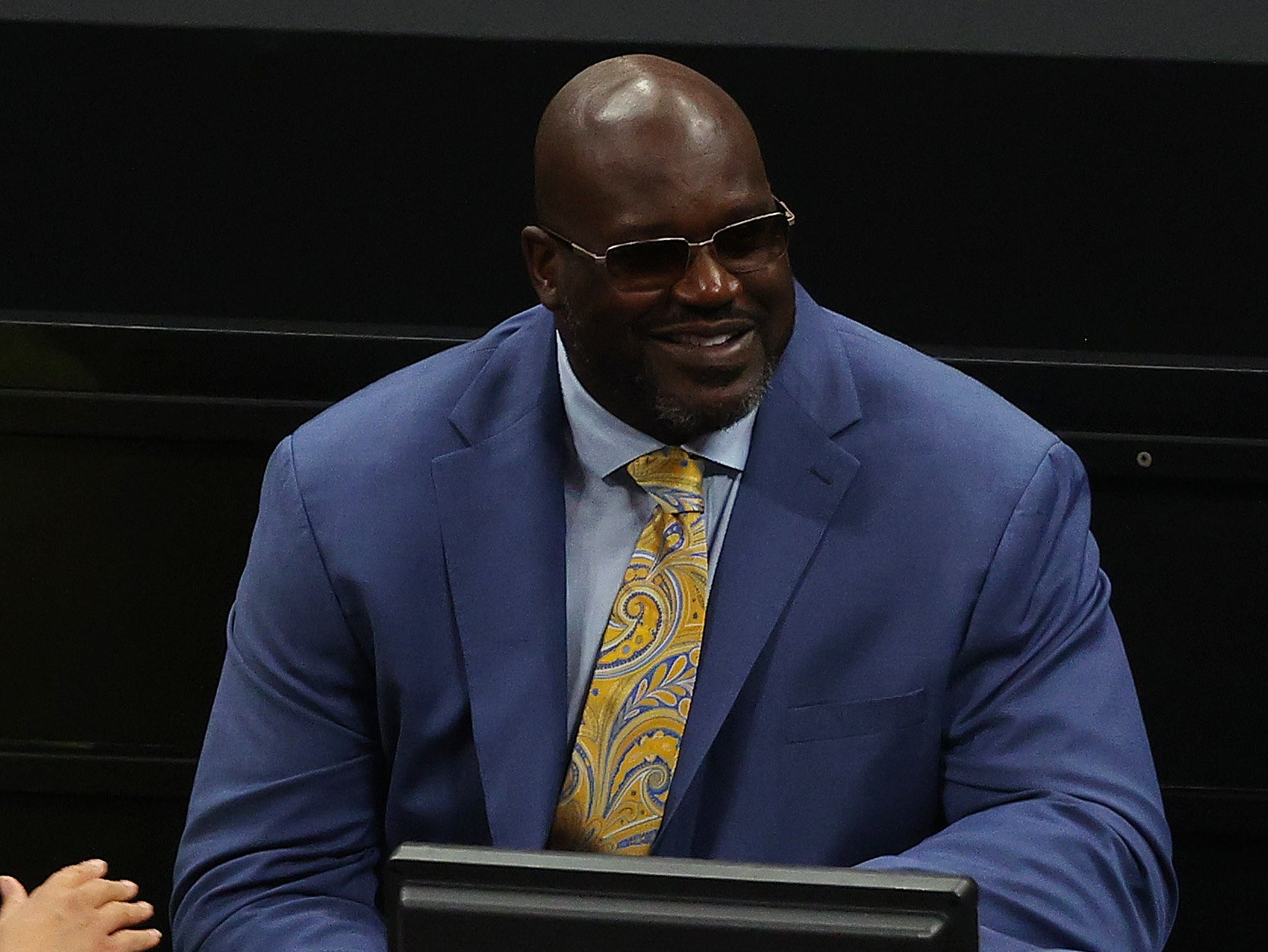 Shaq wearing a suit with sunglasses on smiling