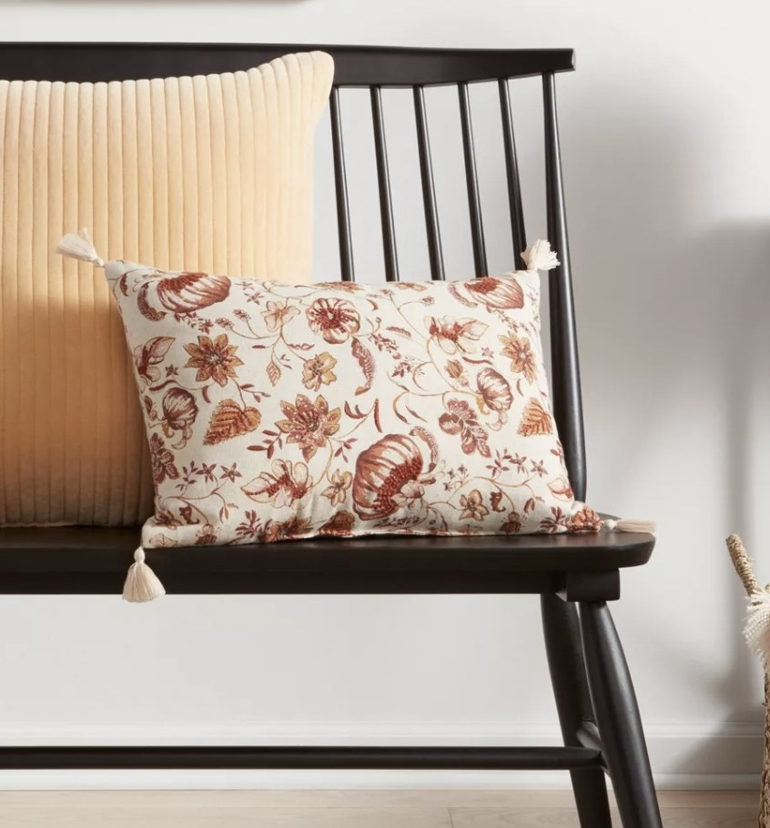 a throw pillow with pumpkin print and tassels