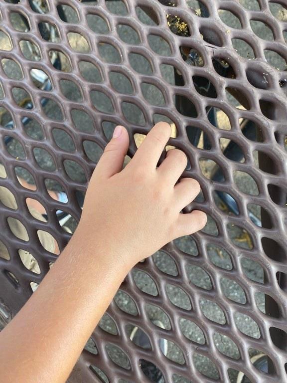 fingers stuck through a woven table