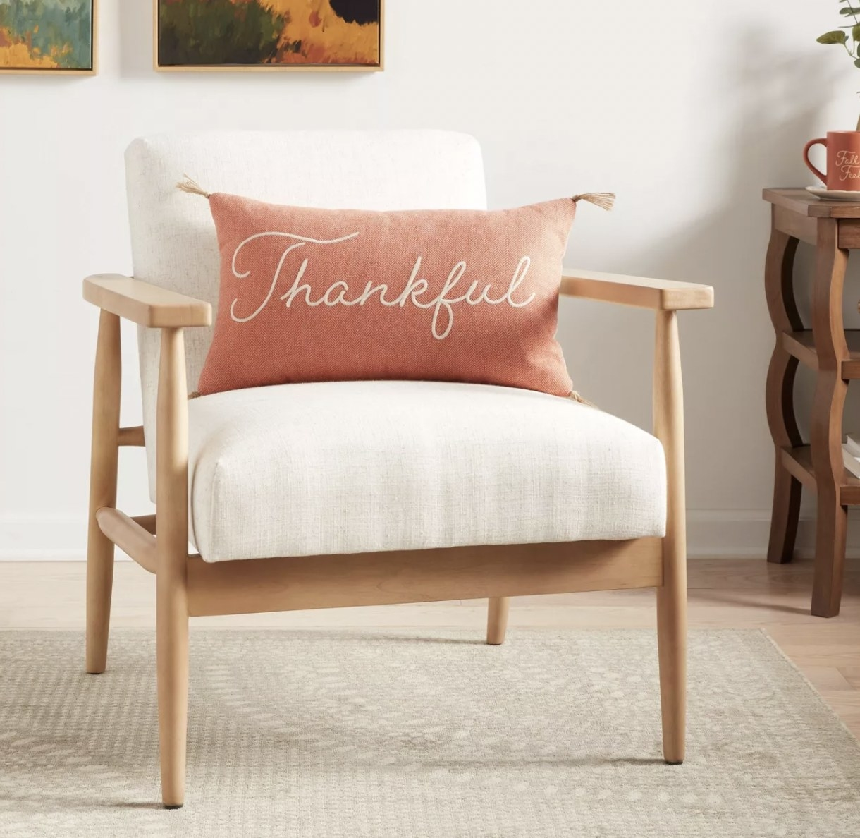 """a salmon colored pillow that says """"thankful"""" in white script"""