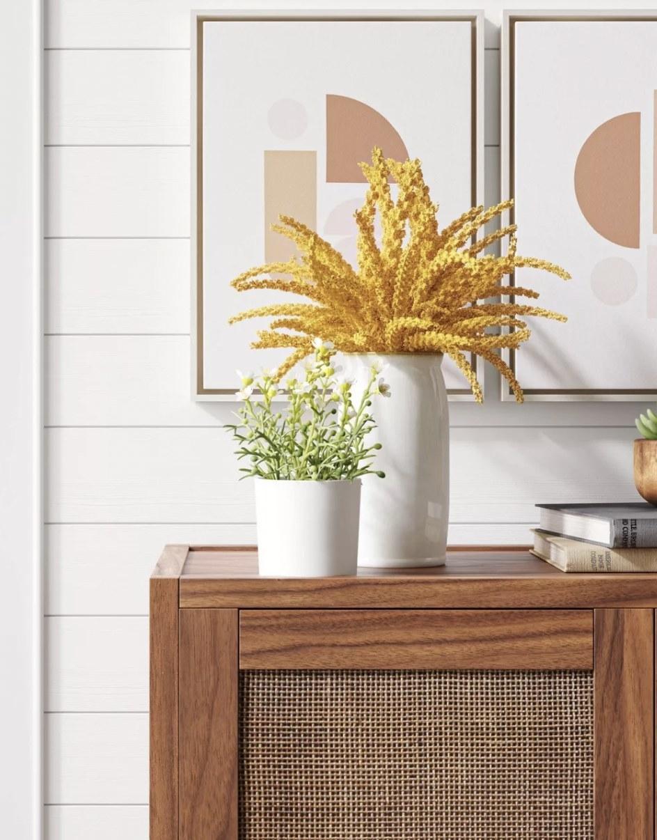 a yelllow faux goldenrod plant arrangement in a ceramic planter