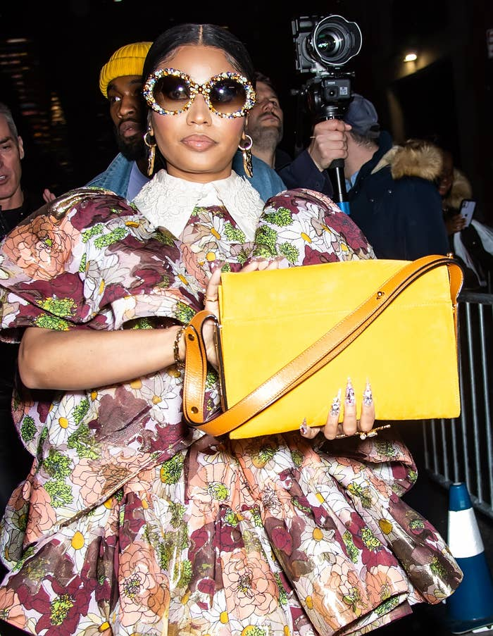Nicki Minaj carries a purse as she walks down the street in a floral print dress and large sunglasses