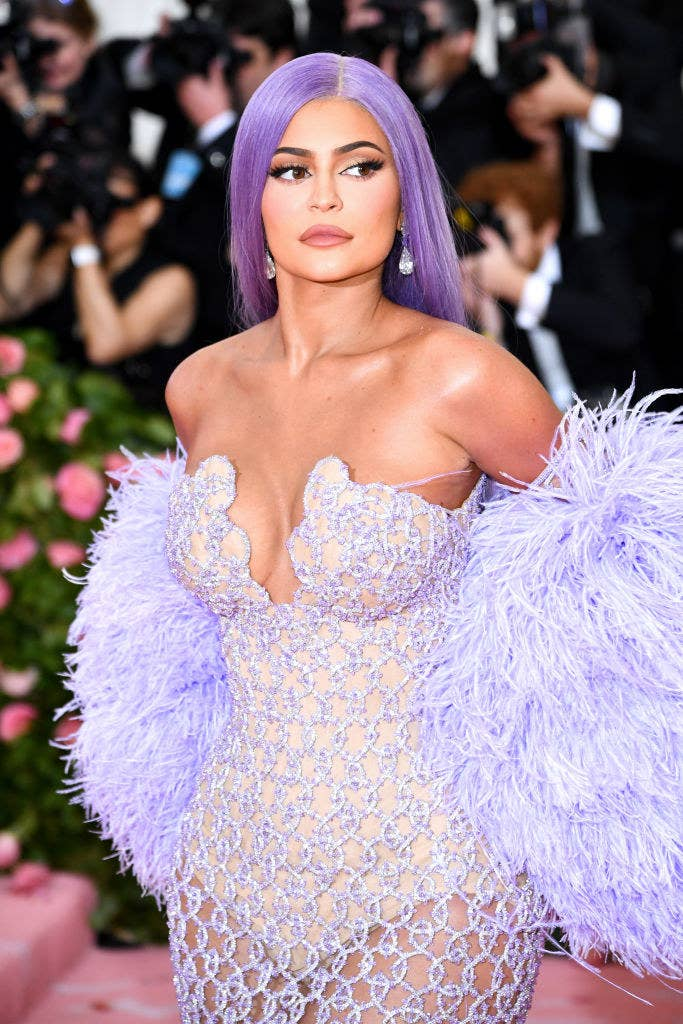 Kylie Jenner attends The 2019 Met Gala Celebrating Camp: Notes on Fashion in a strapless see-through gown with a matching feathered stole