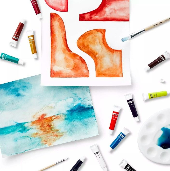 The paint tubes scattered around two watercolor paintings
