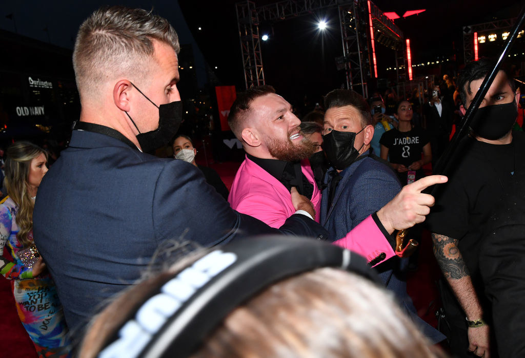 Conor being held back by security
