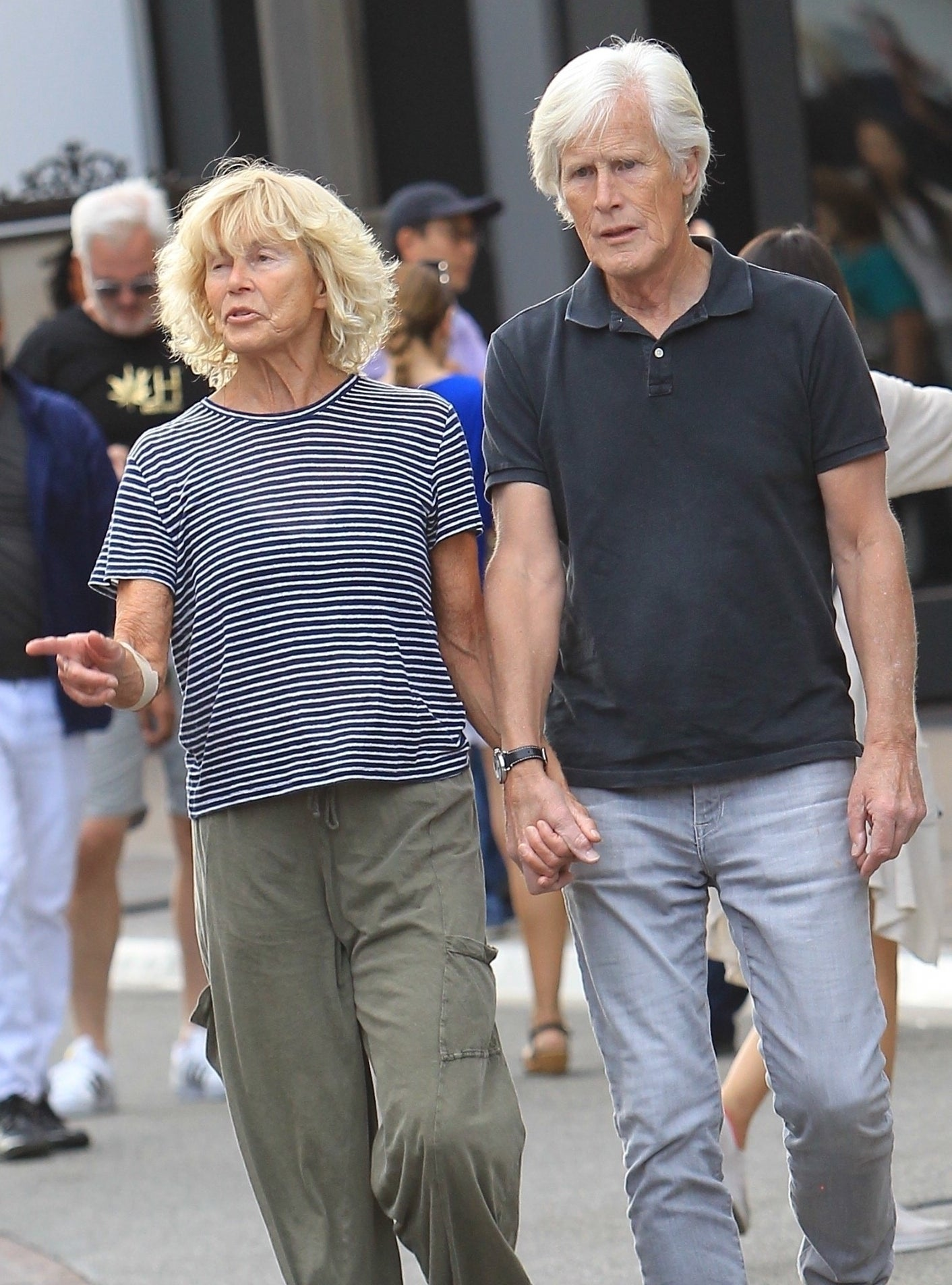 Suzanne and Keith holding hands and walking together, dressed casually