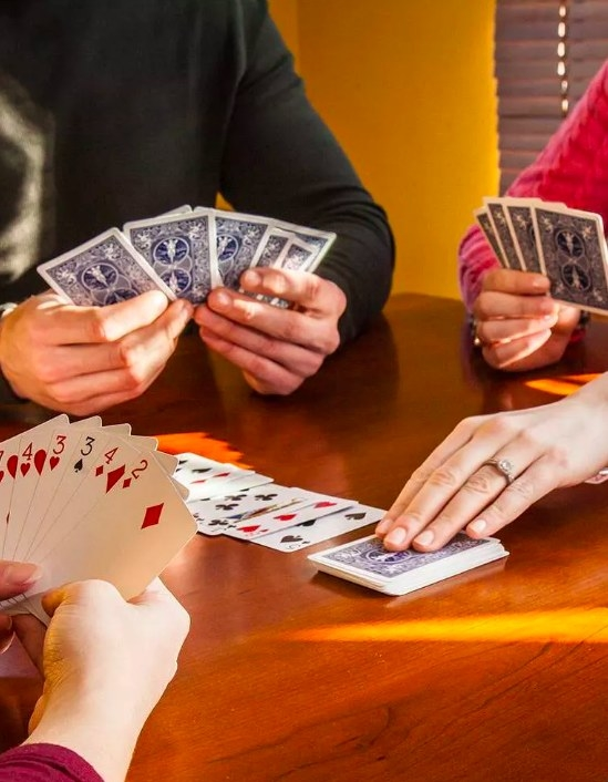 A group of friends playing a card game with the deck