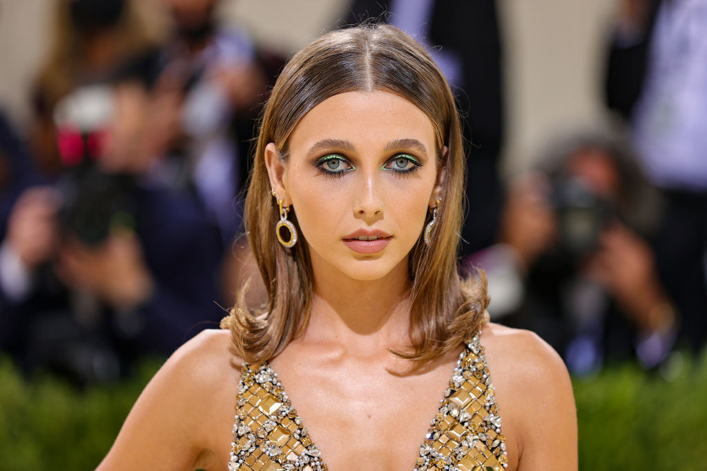 A close up of Emma Chamberlain shows her colorful eyeshadow and dangling earrings