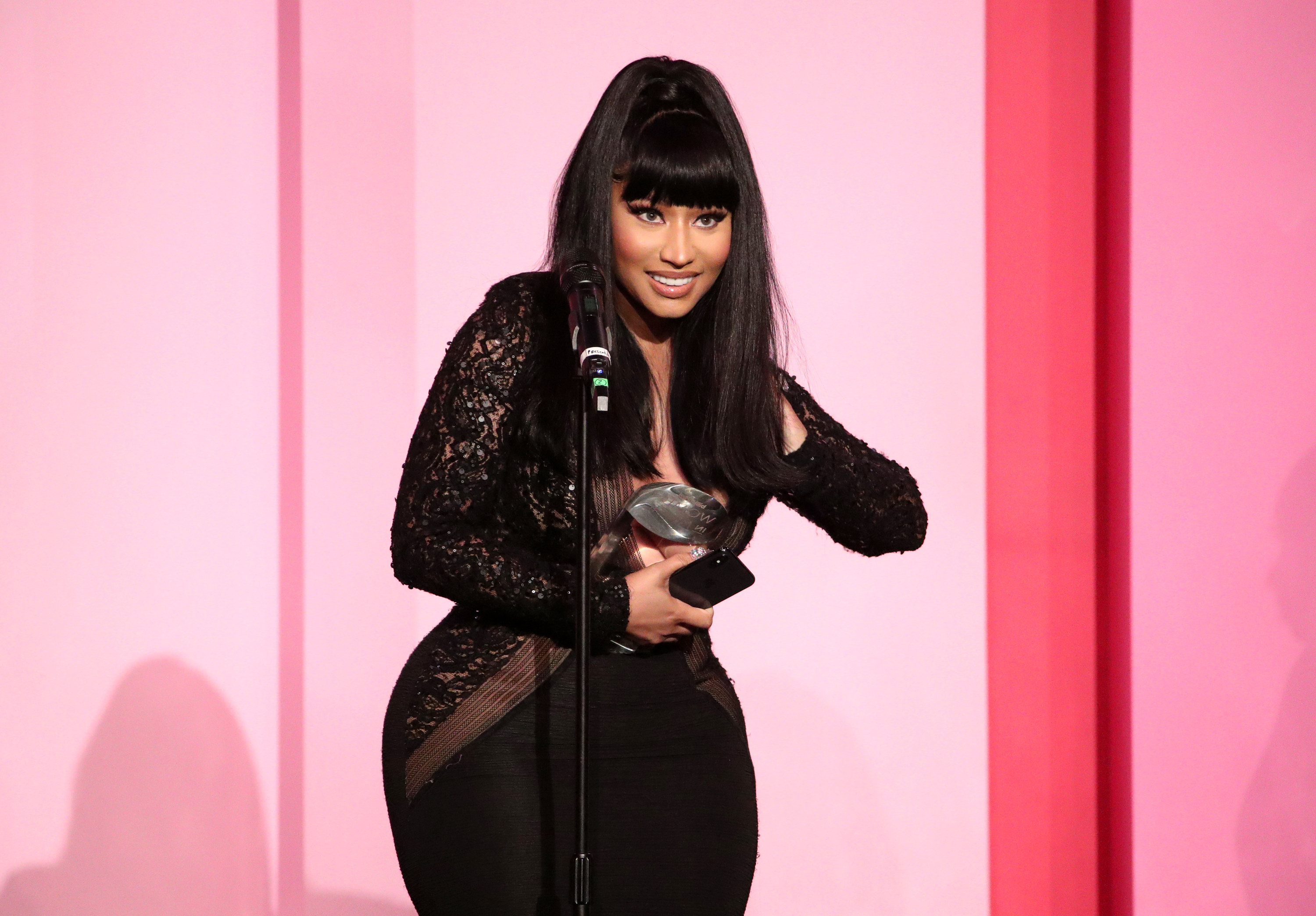 Minaj stands in front of a microphone while accepting an award