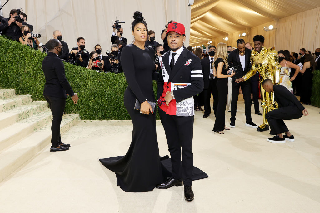 Chance the Rapper wear a dark suit with colorful pattern patches sewn towards the bottom of the jacket andKirsten Corley wears a floor length long sleeve gown