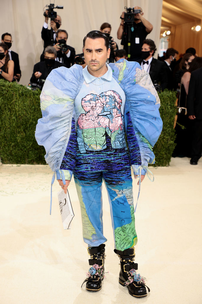 Dan Levy attends The 2021 Met Gala in a printed shirt/pant combo that features two people kissing and a map of the world