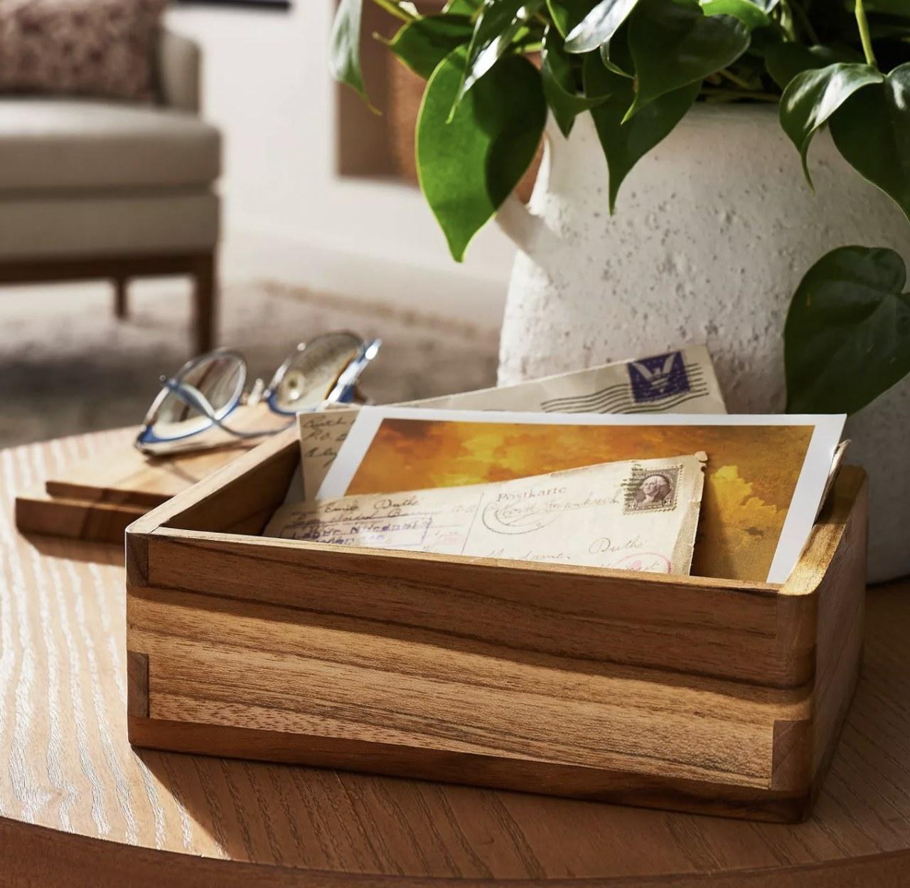 a teak wood box holding envelopes