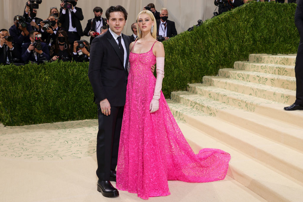 Brooklyn Beckham wears a dark suit and Nicola Peltz wears a thin strap lace brightly colored gown with elbow length gloves