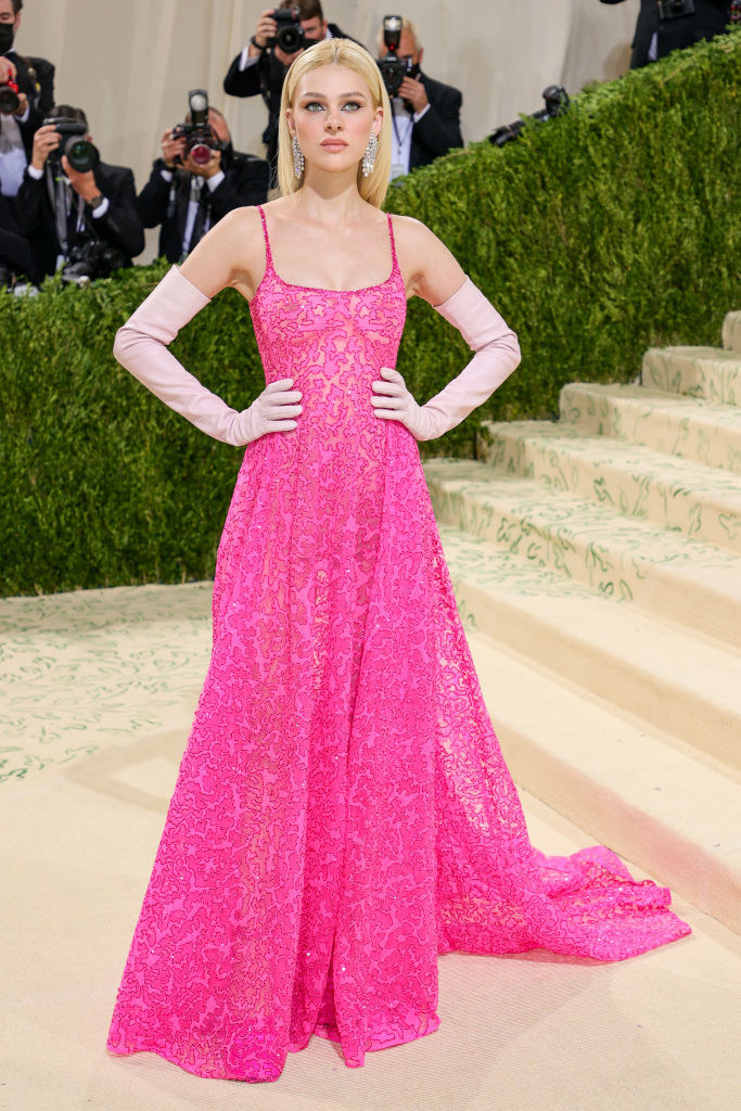 Nicola Peltz attends The 2021 Met Gala in a long brightly colored dress with matching long gloves