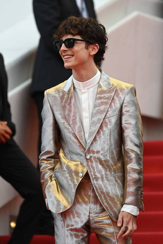 Timothée wearing a metallic suit and sunglasses at an event