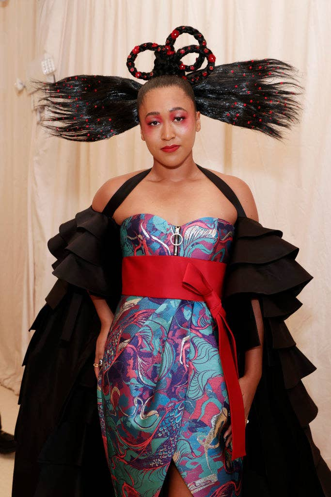 Naomi Osaka attends The 2021 Met Gala in a printed strapless dress with a matching cape and bow at the waist
