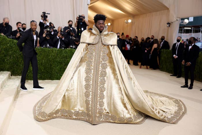 Lil Nas X wears a floor length patterned cape