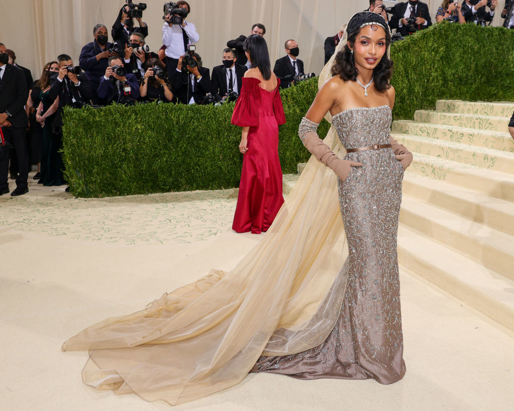 Yara Shahidi attends The 2021 Met Gala in a sparkly strapless fitted gown with a cape, train, and matching gloves