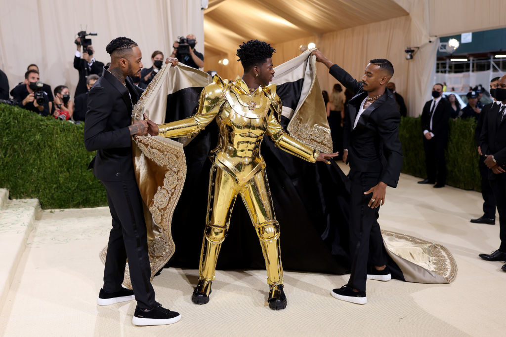 Lil Nas X's cape is taken off by two men to reveal his gold plated suit of armor