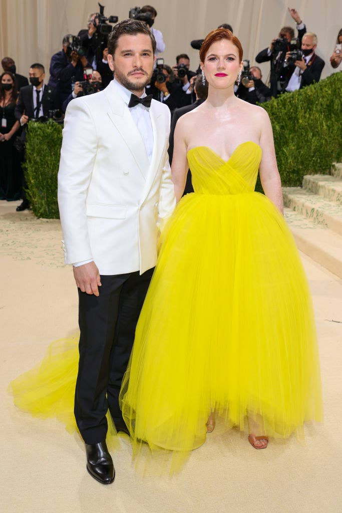 Kit Harrington wears a light colored blazer over dark slacks and Rose Leslie wears a strapless floor length brightly colored gown