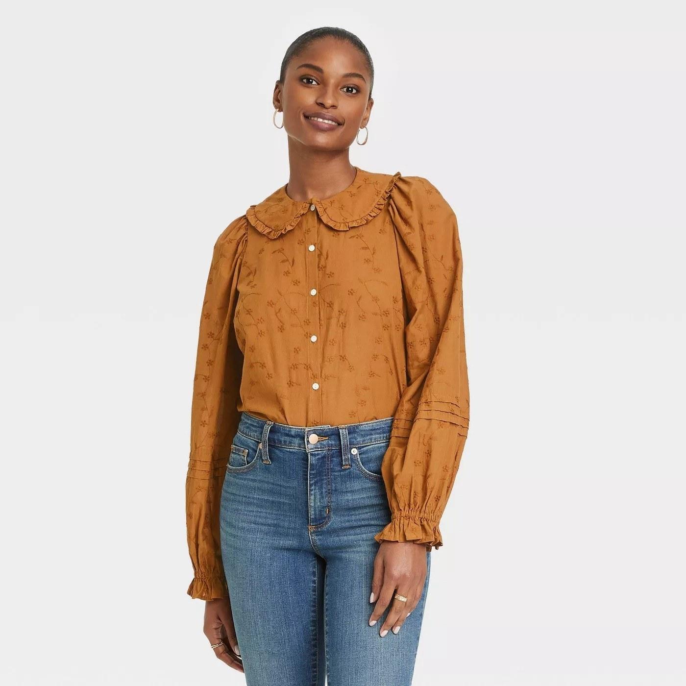 Model wearing orange blouse