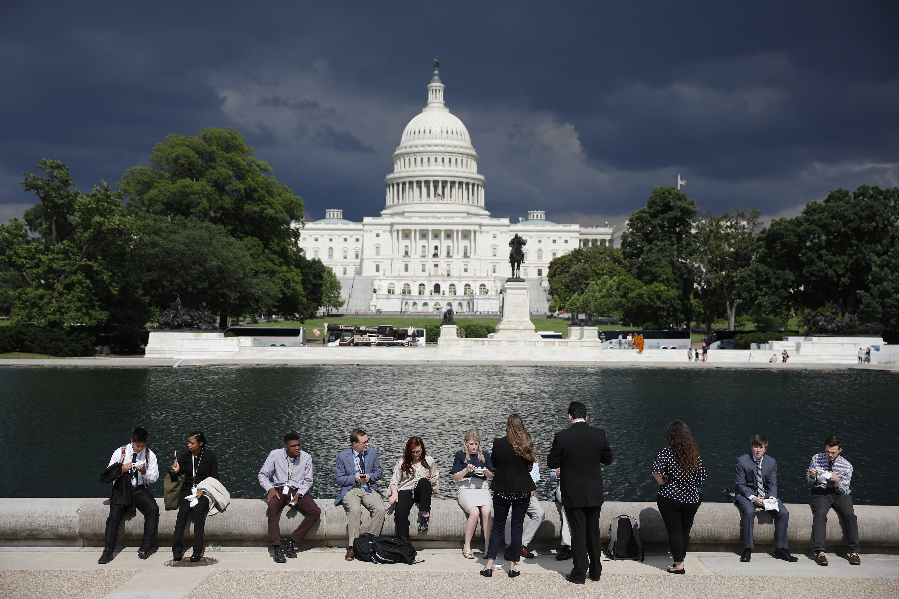 A row of young congressional staffers sit on a ledge, with the US Capitol behind them