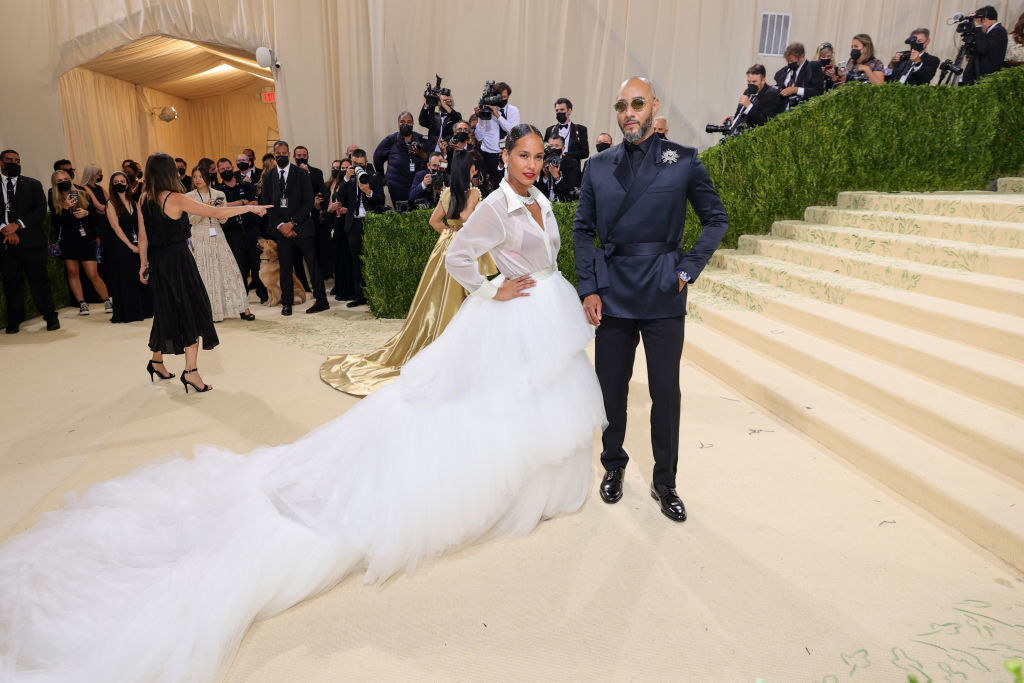 Alicia Keys wears a long sleeve collared gown with a long, ruffle train and Swizz Beatz wears a dark colored suit with a flower on his lapel
