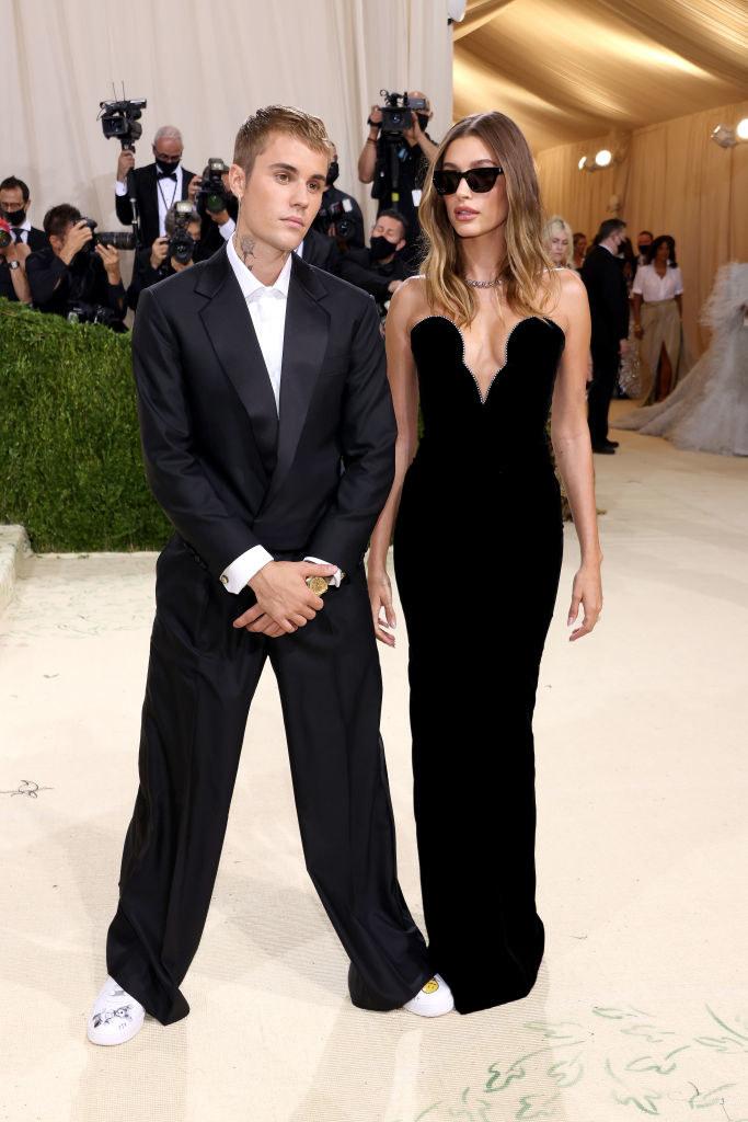 Justin Beiber wears a dark blazer and baggy slacks and Hailey Bieber wears a strapless dark gown