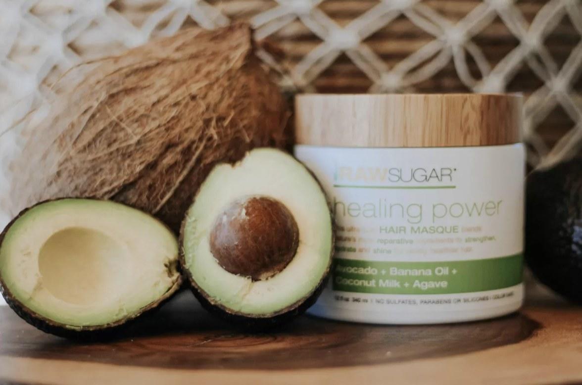 A jar with hair mask, a cut avocado and a coconut
