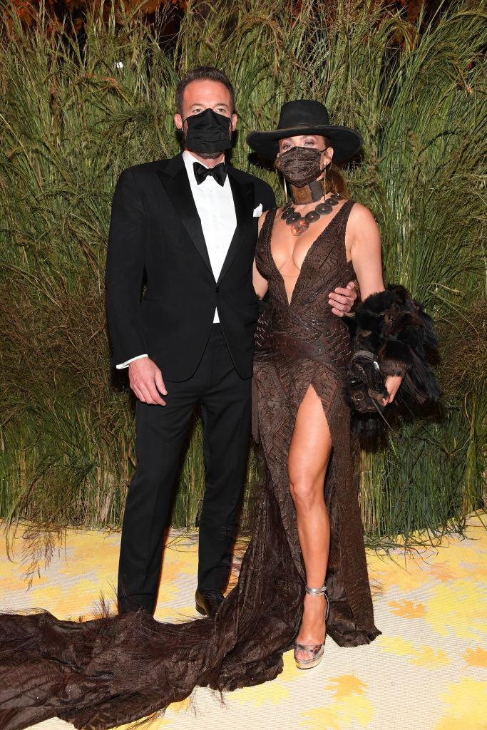 Ben Affleck wears a dark suit and Jennifer Lopez wears a floor length deep v-neck gown