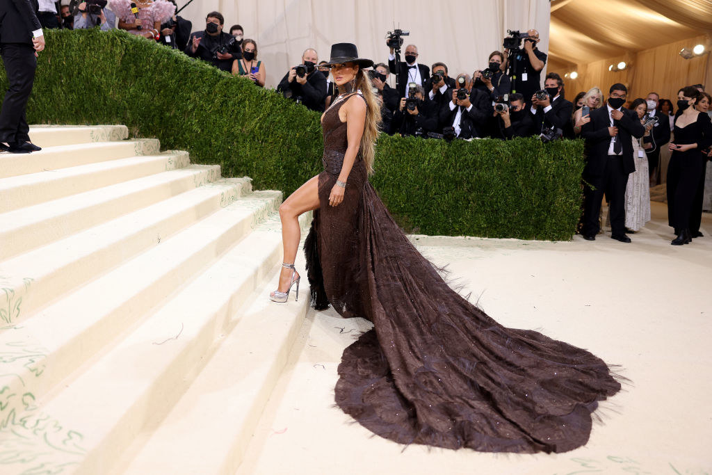 Jennifer Lopez attends The 2021 Met Gala in a long gown with a Western style belt and Stetson hat