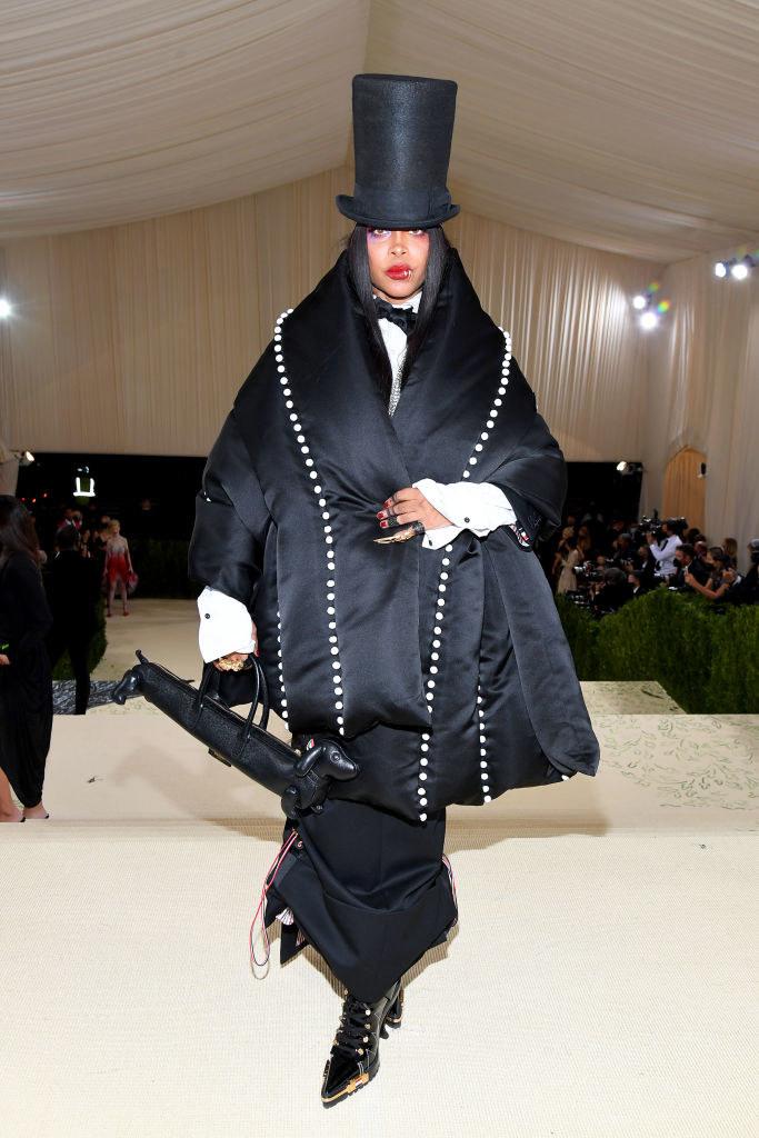 Erykah Badu wears a long dark oversized cape-like coat and a matching top hat