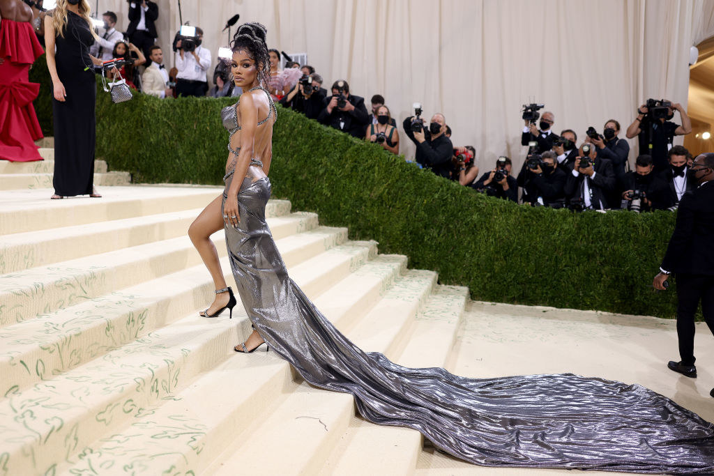 Teyana Taylor wears a gown with a criss-cross bodice that shows off her stomach and a long train