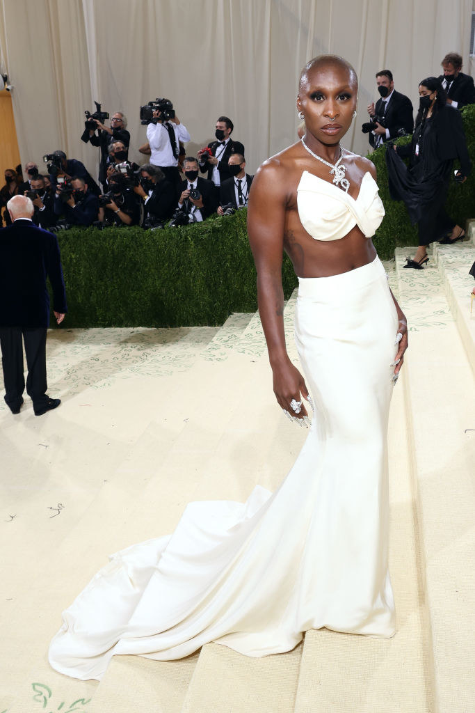 Cynthia Erivo wears a light colored strapless crop top and a matching long skirt