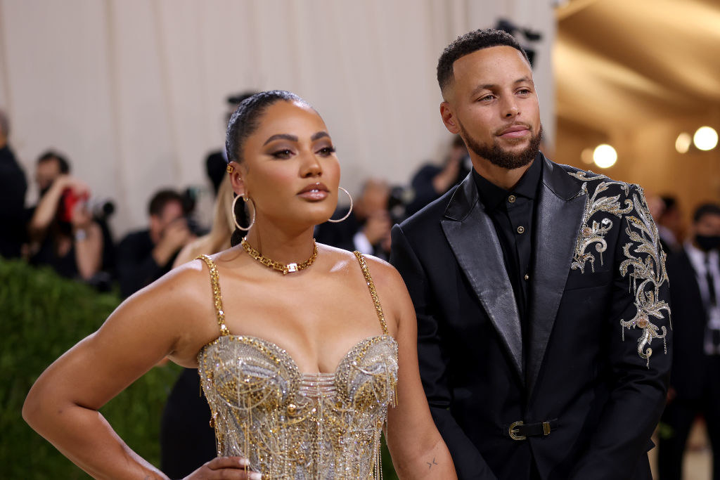 A close up of Ayesha Curry as she poses next to her husband, Stephen