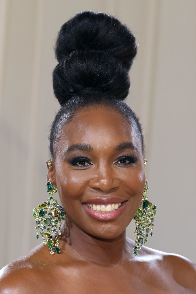 A close up ofVenus Williams as she shows off her dark eye makeup and high bun hairstyle