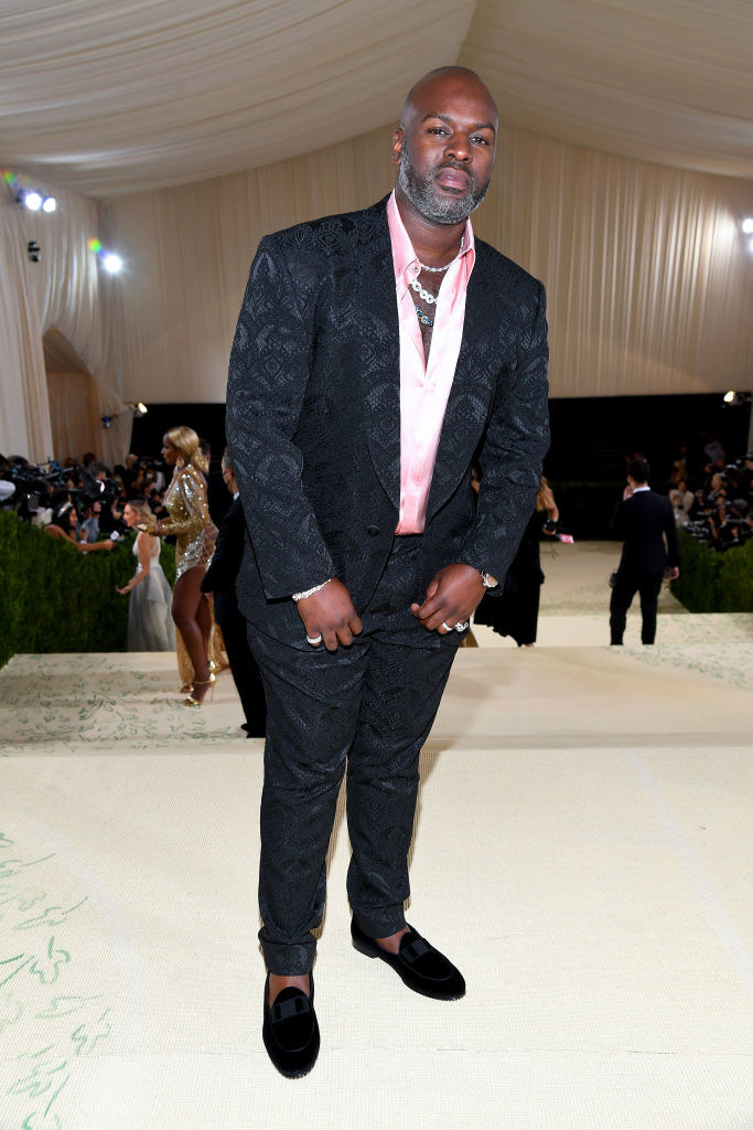 Corey Gamble wears a brightly colored button up shirt under a dark suit jacket and matching slacks