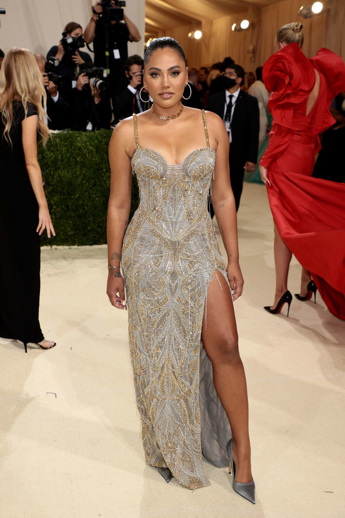 Ayesha Curry wears a floor length thin strap sparkly gown with a slit up her thigh