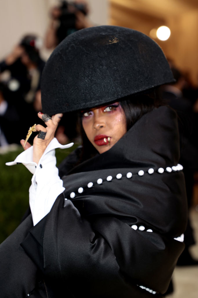 A close up ofErykah Badu as she poses while looking over her shoulder