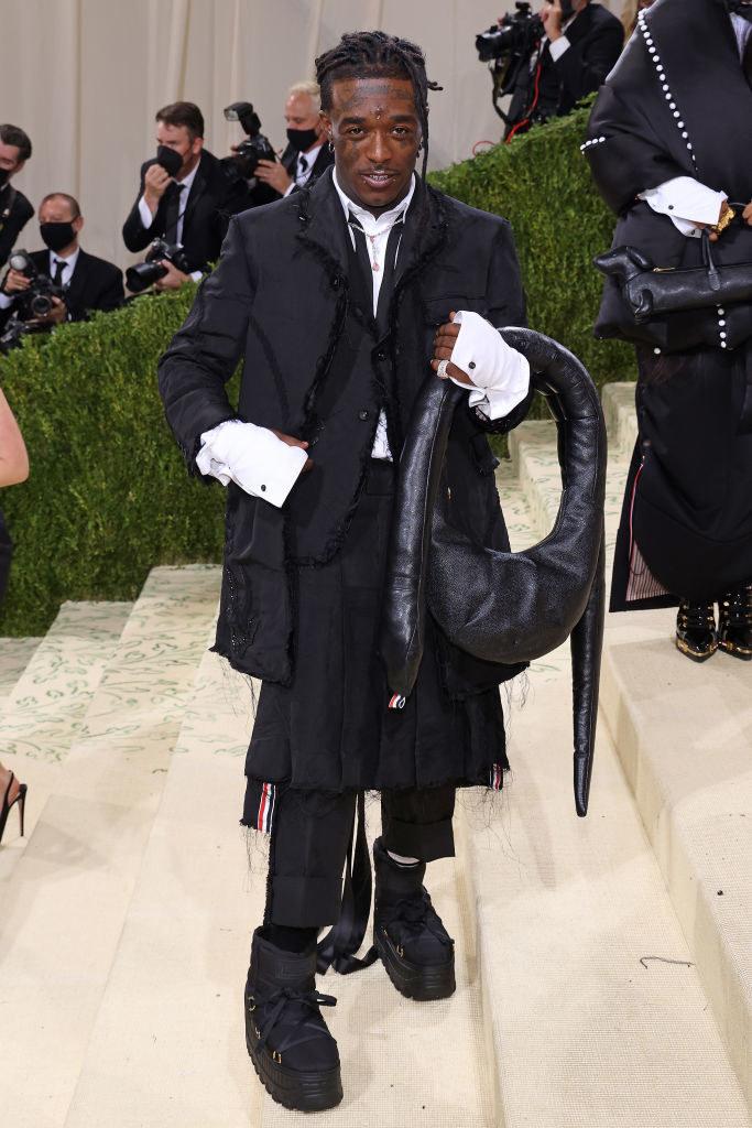 Lil Uzi Vert wears a dark skirt over matching leggings and a matching knee length overcoat