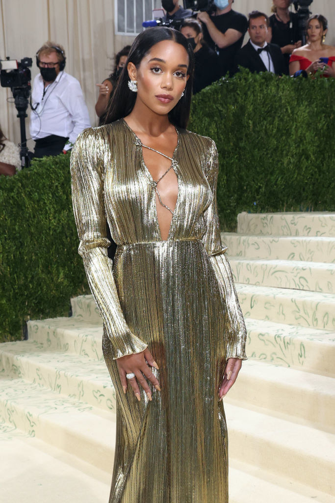 Laura Harrier wears a long sleeve v-neck shiny gown