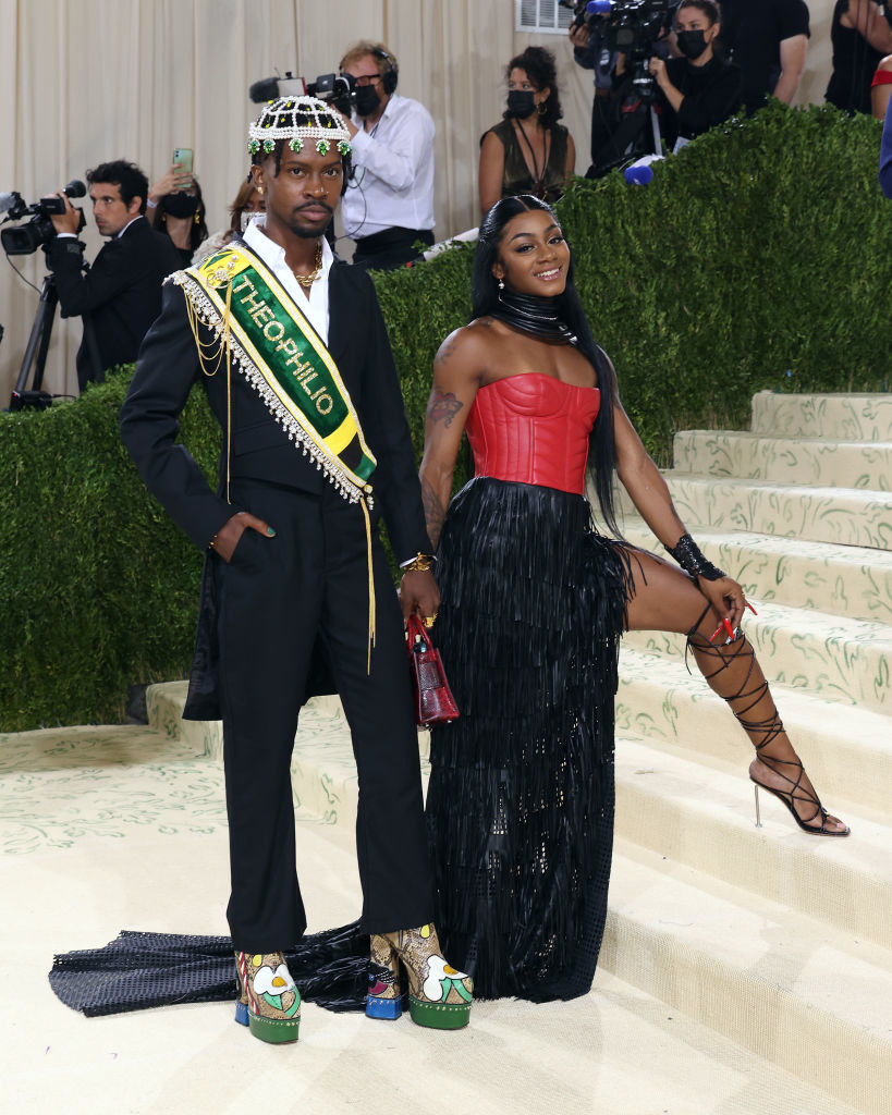 Edvin Thompson wears a dark suit with a bright sparkly slash around his torso and a matching beaded head piece