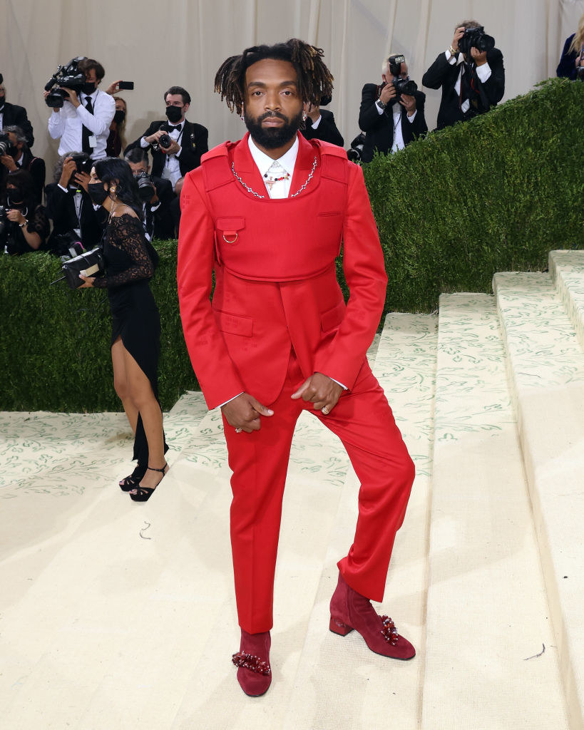 Kerby-Jean Raymond wears a brightly colored suit underneath a matching cropped bulletproof vest