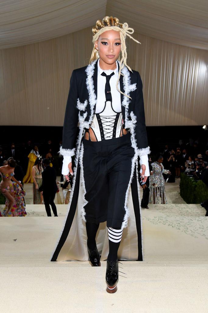 Amandla Stenberg wears a light colored bodysuit tucked into dark knee length slacks under a long overcoat with a train