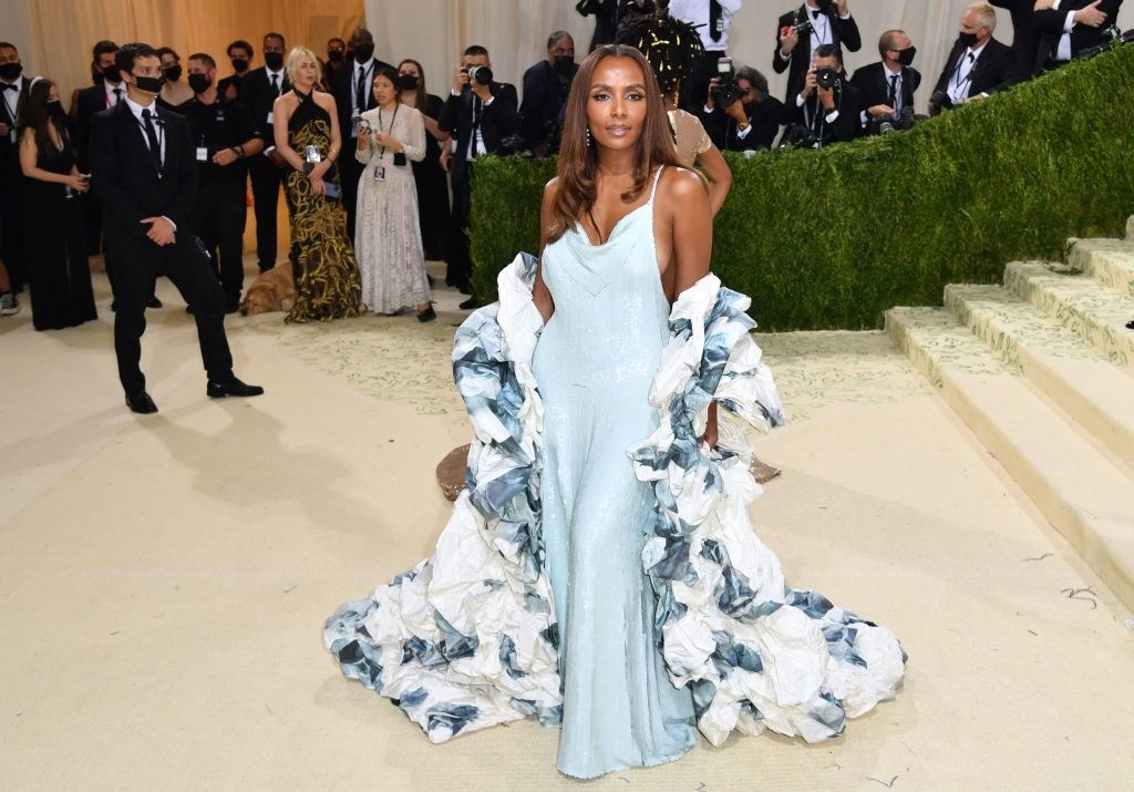 Janet Mock wears a floor length thin strap sparkly gown under a matching ruffle shawl