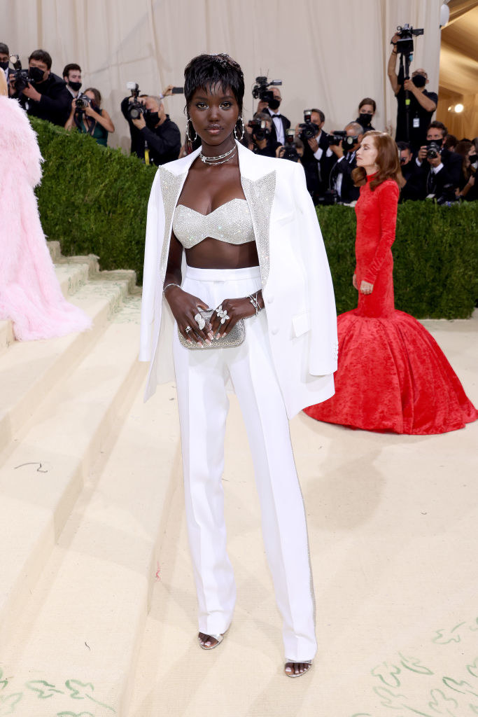 Adut Akech wears a sparkly bandeau and light colored slacks with a matching blazer