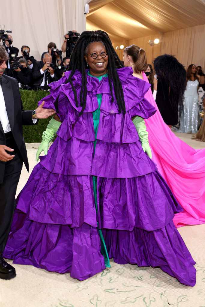 Whoopi Goldberg wears a short sleeve gown with ruffled layers and brightly colored elbow length gloves