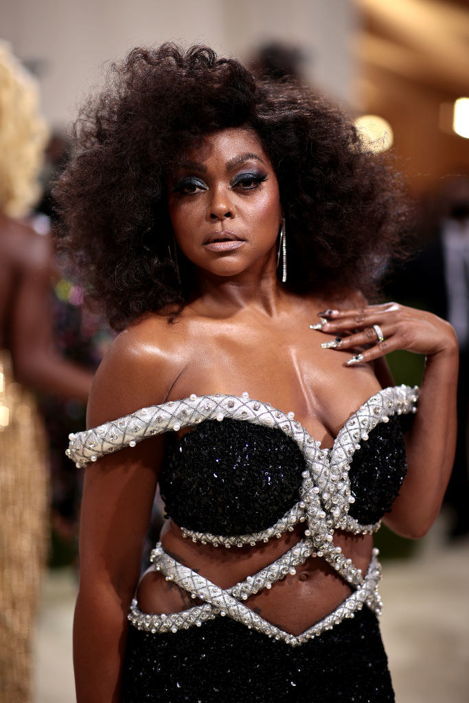 A close up of Taraji P. Henson as she shows off her dark eye makeup and afro