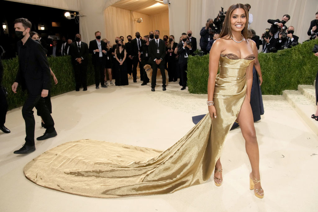 Leyna Bloom wears a strapless shiny gown with a long train